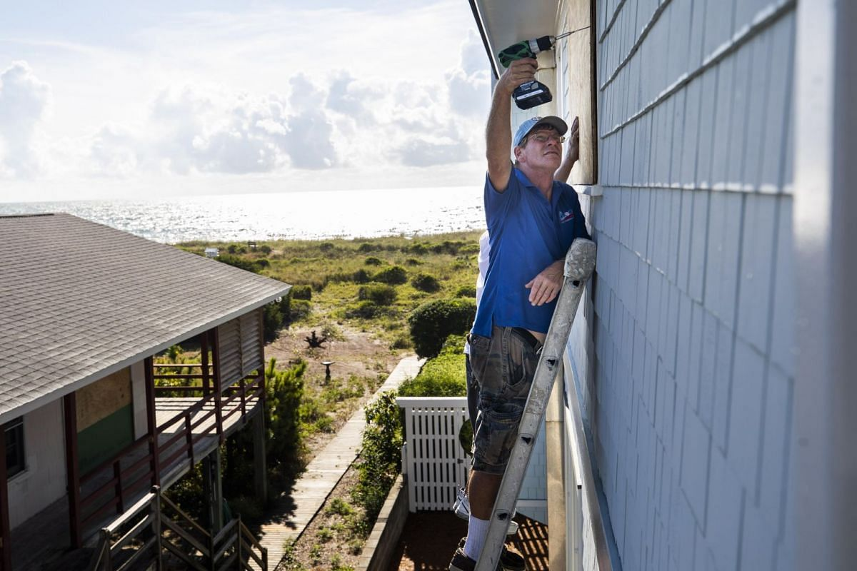 Resident Butch Beaudry drilling a wooden plank over the window of an oceanfront home before Hurricane Florence arrives and strikes Wrightsville Beach, North Carolina.