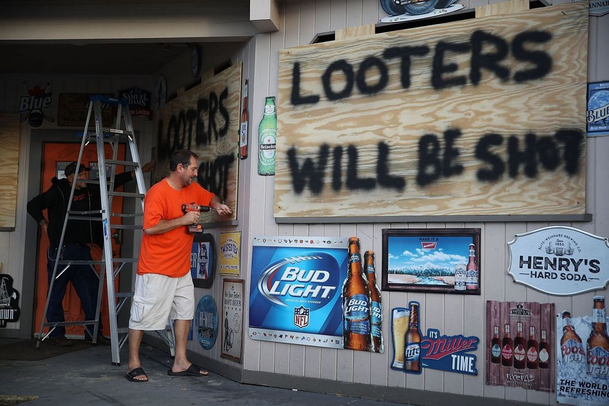 """Doug Lewis (left) and Chris Williams using plywood with the words """"Looters will be shot"""" to cover the windows of Knuckleheads bar as they try to protect the business ahead of Hurricane Florence's arrival."""
