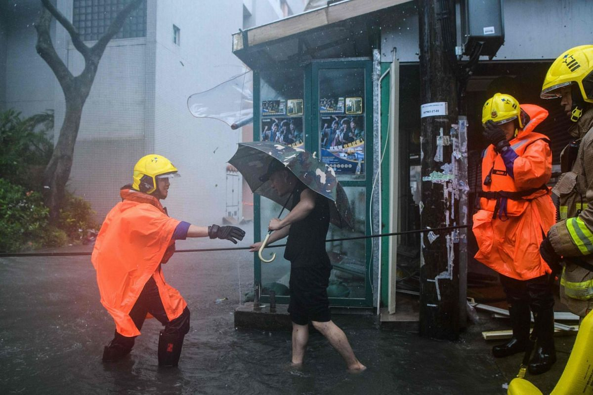 Rescue workers help a man cross a flooded street in the village of Lei Yu Mun as Typhoon Mangkhut slams into Hong Kong on Sept 16, 2018.