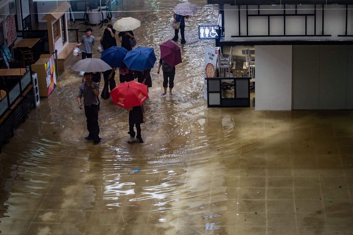 People walk through a flooded shopping mall in Heng Fa Chuen, a residential district near the waterfront in Hong Kong, during Typhoon Mangkhut on Sept 16, 2018.