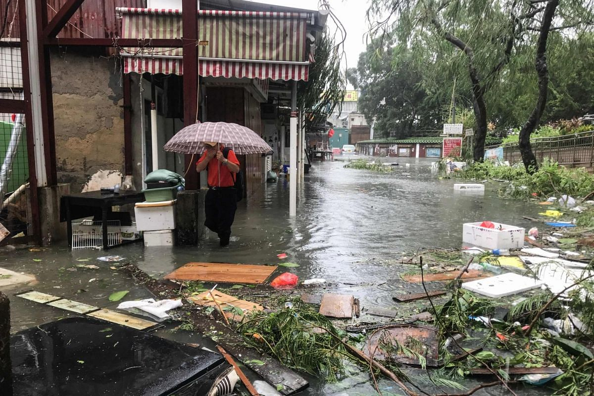 A man wades through floodwaters in the village of Lei Yu Mun during Typhoon Mangkhut in Hong Kong on Sept 16, 2018.