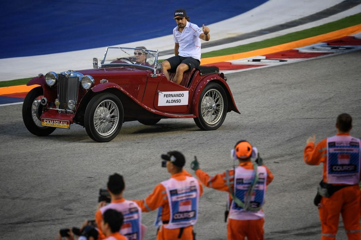 McLaren's Fernando Alonso gestures from a vintage car during the drivers' parade ahead of the 2018 Singapore Airlines Singapore Grand Prix on Sept 16, 2018.