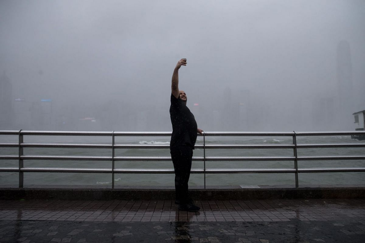 A man takes selfies on the Victoria Harbour waterfront in Hong Kong during Typhoon Mangkhut on Sept 16, 2018.