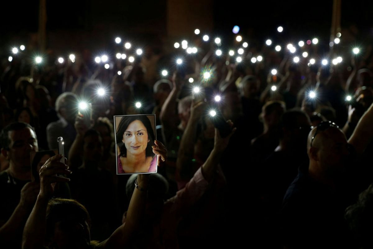 People hold up photos of assassinated anti-corruption journalist Daphne Caruana Galizia and torches on mobile phones during a vigil to mark eleven months since her murder in a car bomb, in Valletta, Malta September 16, 2018.