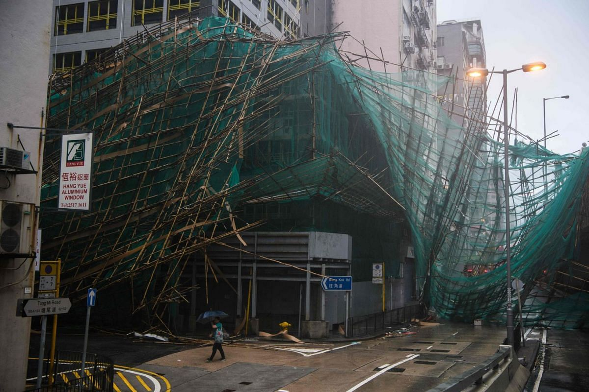 A woman uses her umbrella as she walks past collapsed bamboo scaffolding hanging from a building during Super Typhoon Mangkhut in Hong Kong on September 16, 2018.