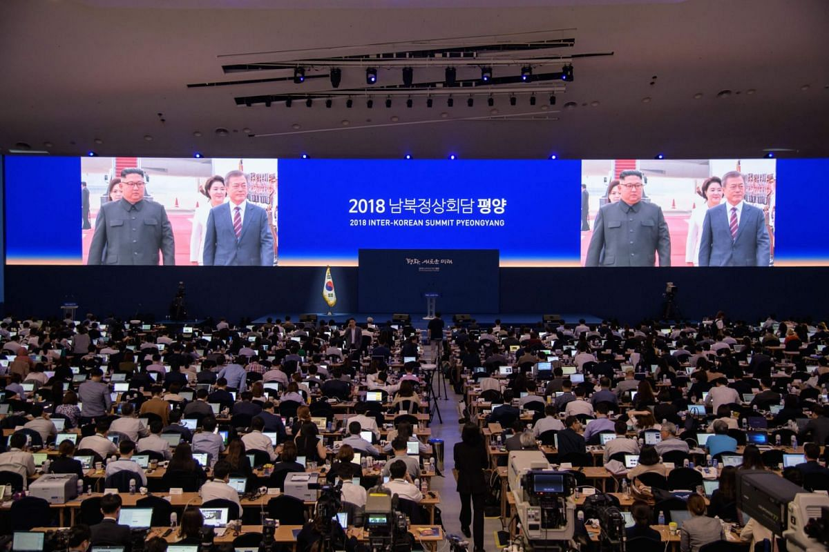 Television screens broadcast images of South Korea's president Moon Jae-in walking with North Korean leader Kim Jong Un after arriving in Pyongyang, at an inter-Korean summit press centre in Seoul, on Sept 18, 2018.