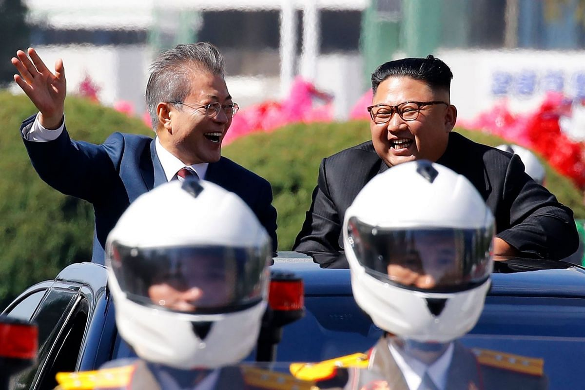 North Korean leader Kim Jong Un (right) and South Korean President Moon Jae-in wave to Pyongyang citizens from an open-topped vehicle as they drive through Pyongyang, on Sept 18, 2018.