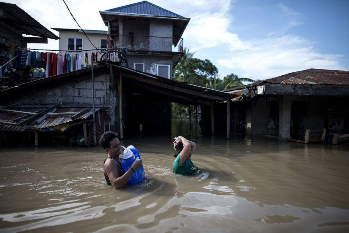 Residents wade through a flooded street in the aftermath of Super Typhoon Mangkhut in Calumpit, the Philippines, on Sept 17, 2018.