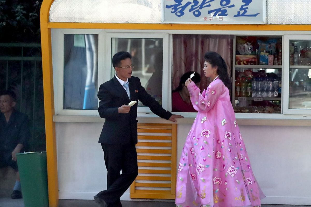 North Korean people eat ice cream in front of a kiosk in Pyongyang, North Korea, on Sept 18, 2018.