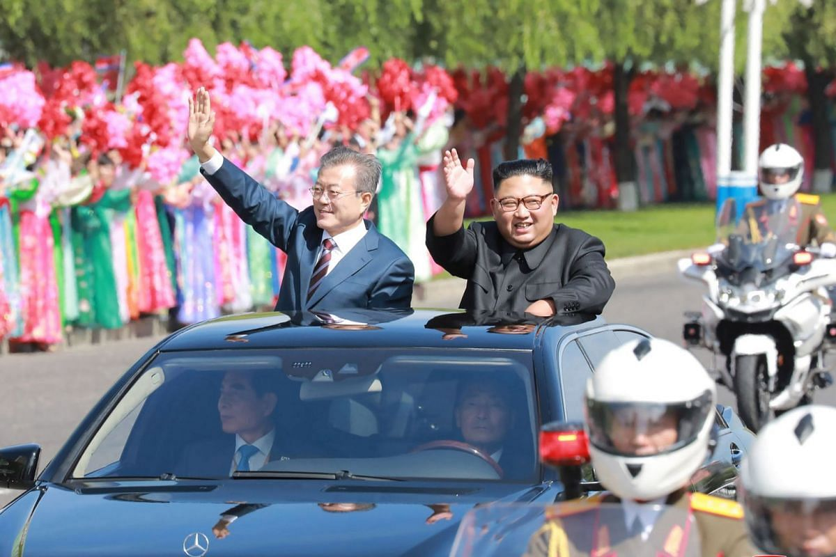 This picture taken on September 18, 2018 and released by Korean Central News Agency (KCNA) via KNS shows North Korean leader Kim Jong Un (R) and South Korean President Moon Jae-in (L) waving to Pyongyang citizens from an open-topped vehicle as they d