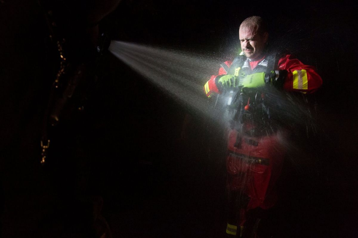 Steven Barker, a firefighter with the Spring Lake Fire Department, is sprayed with water to decontaminate his uniform after a rescue mission during response efforts in the aftermath of Hurricane Florence in Spring Lake, North Carolina, September 18,