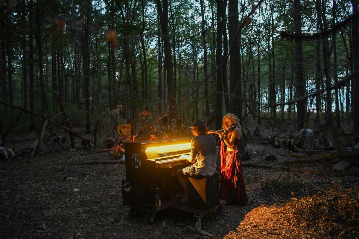 People play music during a mourning ceremony in the Hambach Forest on September 20, 2018 near Kerpen, a day after a journalist died during a major clearance operation of a camp of environmentalists set up to block the expansion of an open-pit coal mi