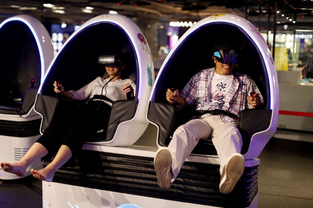 People try a VR Cinema simulator at a shopping mall in Bangkok, Thailand September 20, 2018. PHOTO: REUTERS