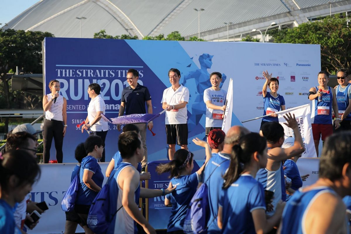 On stage to flag off the 5km category of the ST Run: (from left) emcee Kelly Latimer; ST sports editor Lee Yulin, chief marketing officer of LGI Lim Shyong Piau, deputy managing director of Panasonic Jiro Nakami, deputy CEO of SPH Anthony Tan, Minist