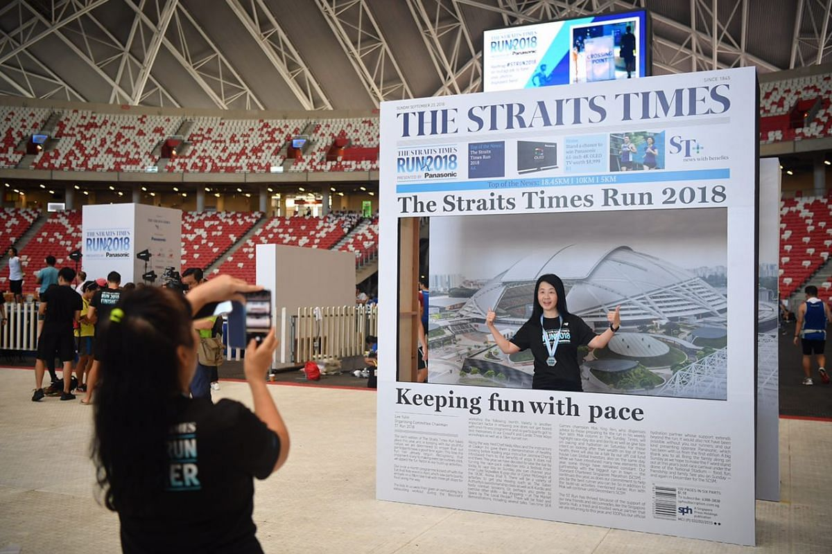 10km run participant, Madam Lily Ong, 55, taking a photo with the front page of The Straits Times.