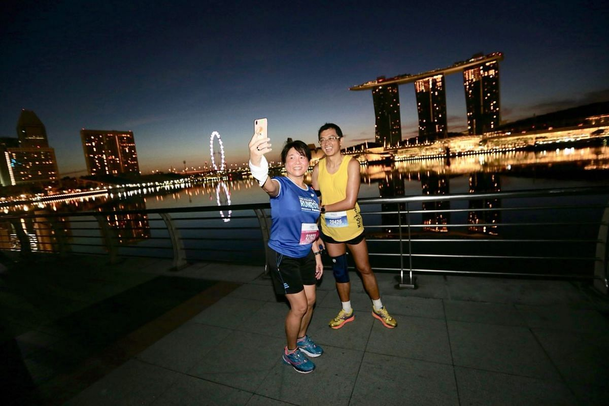 """Madam Tan Sew Yong, 46, with her husband Yan Wing Kin, 47, taking a wefie at Merlion Park during the 18.45km run. """"The scenery is so beautiful! This is my first time taking part in ST Run. If not for the run, I will have not woken up so early to be h"""