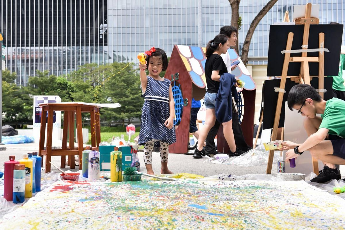 Margaret Oh, five, spraying paint onto a canvas at Colour of the Ages booth by Dunman High students. The yellow-coloured water in the water gun that she is holding represents happiness.