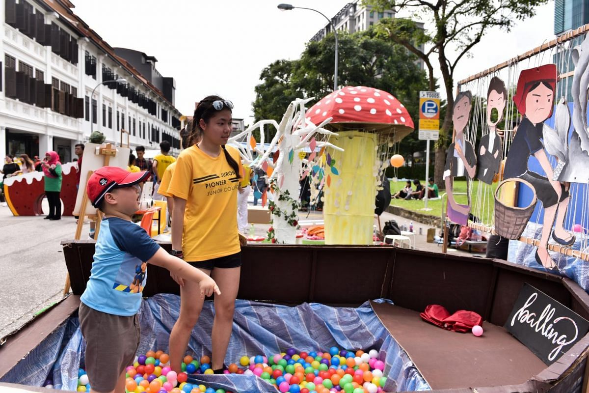 Cai Yu Kai (left), five, throwing balls at the Balling booth by Pioneer Junior College (PJC), as PJC student Stacey Lim, 17, assists him. This activity aims to encourage people to have fun and relax at the ball pit.