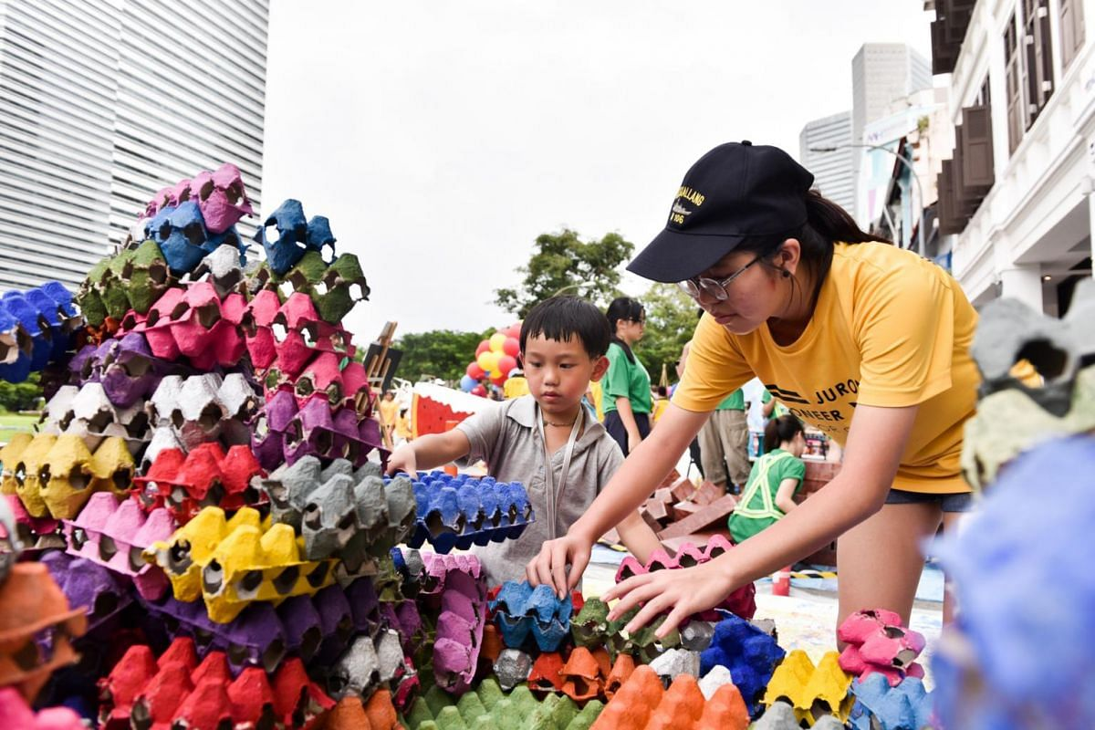 Royce Chan, five, at the Build-A-Tama booth by Pioneer Junior College. He is assisted by PJC student Loke Ai Ning, Grace.