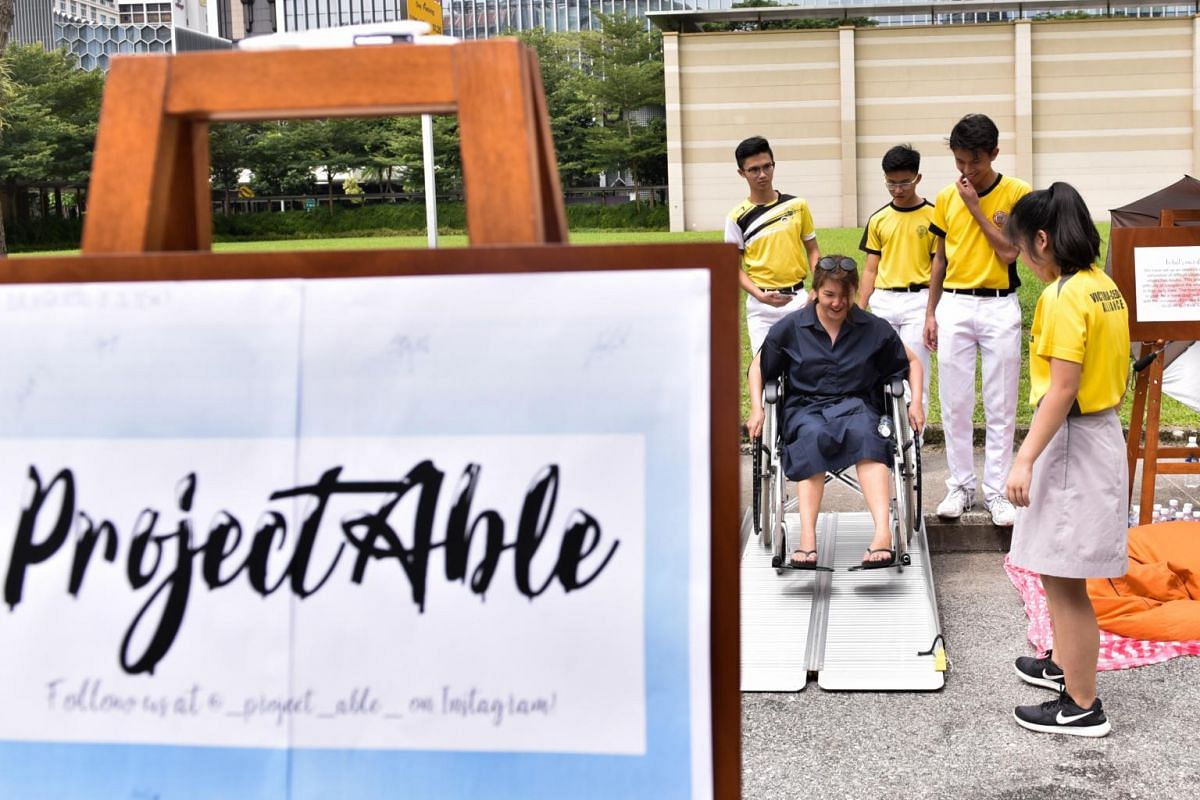 Ms Megan Miao, 26, tries to maneuver herself up the slope on the wheelchair, as part of the activity organised by Victoria School's ProjectAble.