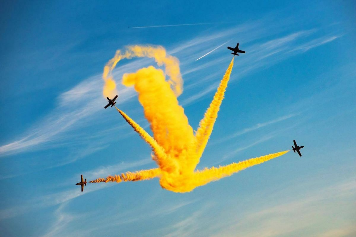 Aircrafts perform and spray yellow couloured smoke during the 25th anniversary of the 'Festa al Cel' Airshow in Lleida, Spain, on Sept 22, 2018.