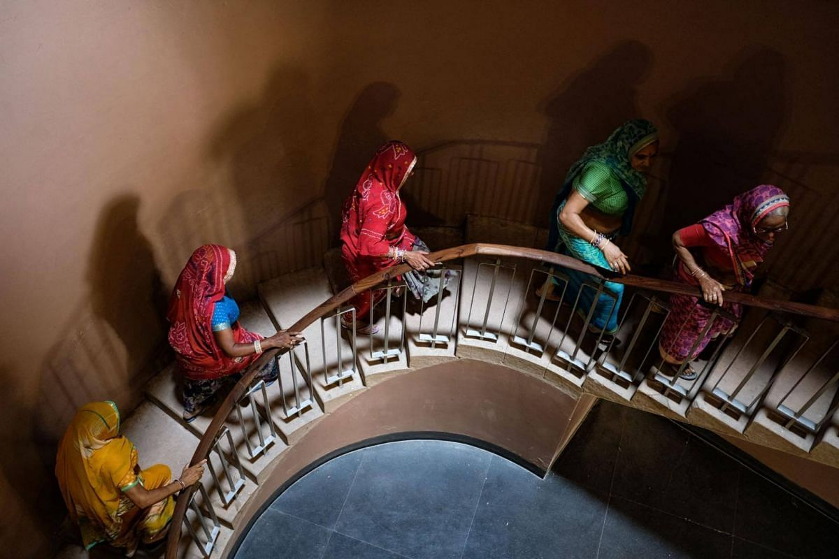 Indian women walk up stairs while visiting Mehran Fort in Jodhpur, on Sept 22, 2018.