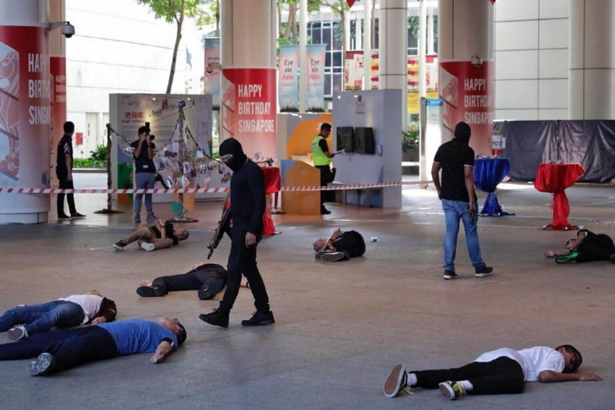 Masked attackers walk among casualties during Exercise Heartbeat at the National Library on Sept 25, 2018.