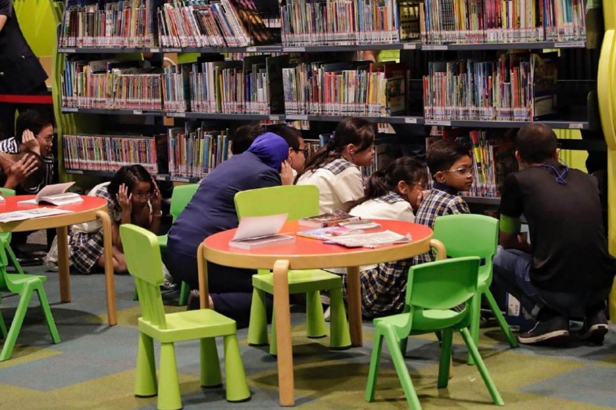 School children take cover as a masked attacker storms into the children's section of the library during Exercise Heartbeat at the National Library on Sept 25, 2018.