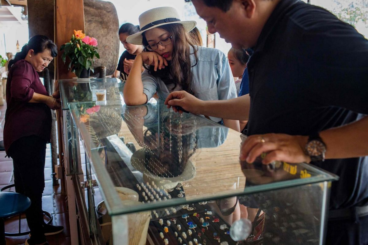 Visitors look at bracelets, figurines made of ivory and jewellery with elephant hair for sale at a shop in a tourist resort in Lien Son town, Dak Lak province.