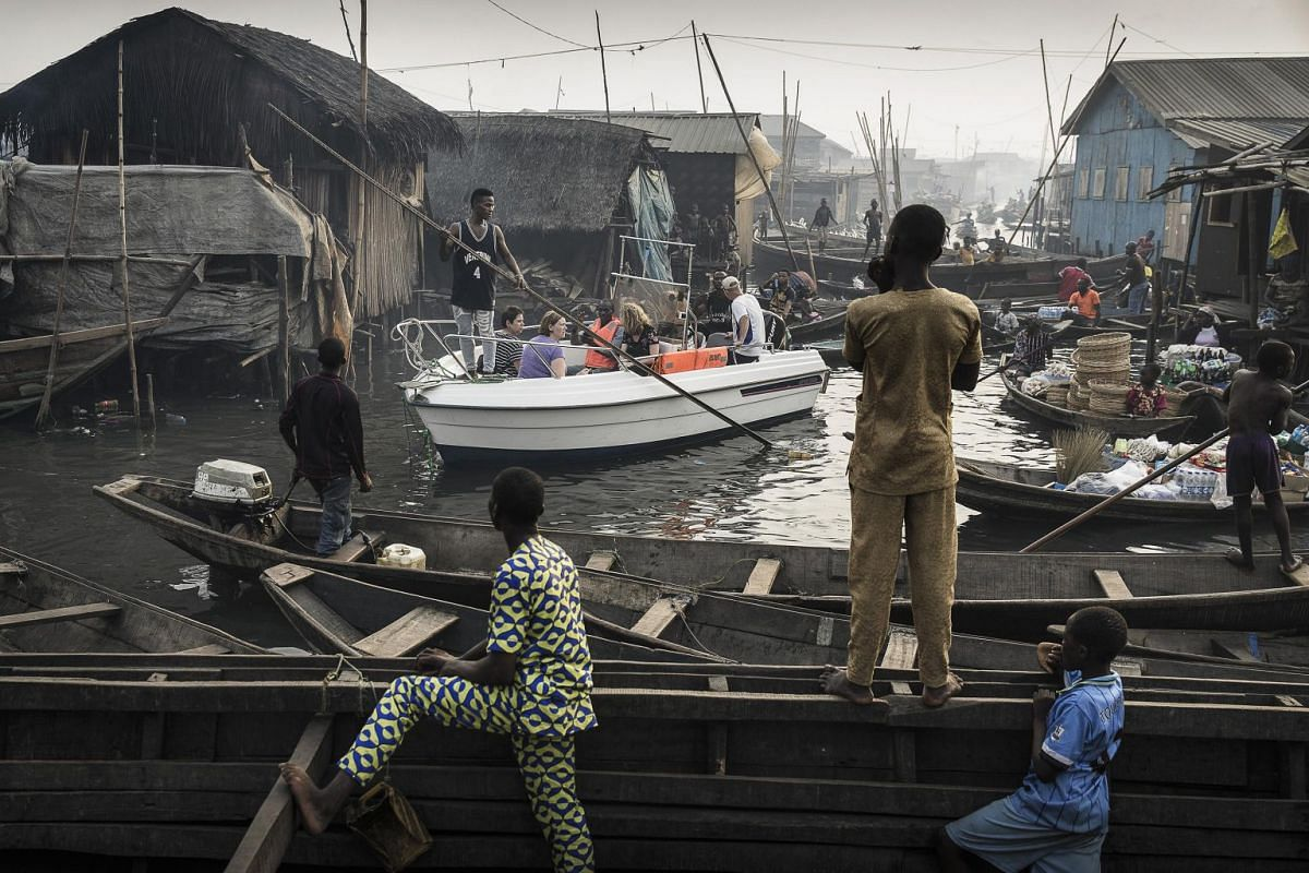 A boat with tourists from Lagos Marina is steered through the canals of the Makoko community - an ancient fishing village that has grown into an enormous informal settlement - on the shores of Lagos Lagoon, Lagos, Nigeria, on Feb 24, 2018. Makoko has