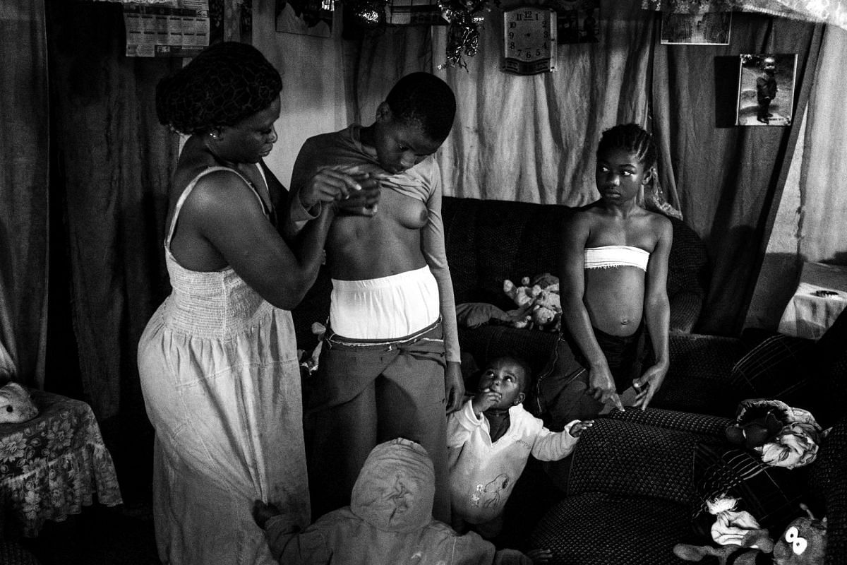 Veronica, 28, massages the breasts of her daughter Michelle, 10, while her other children watch, in East Cameroon, on Nov 7, 2016.