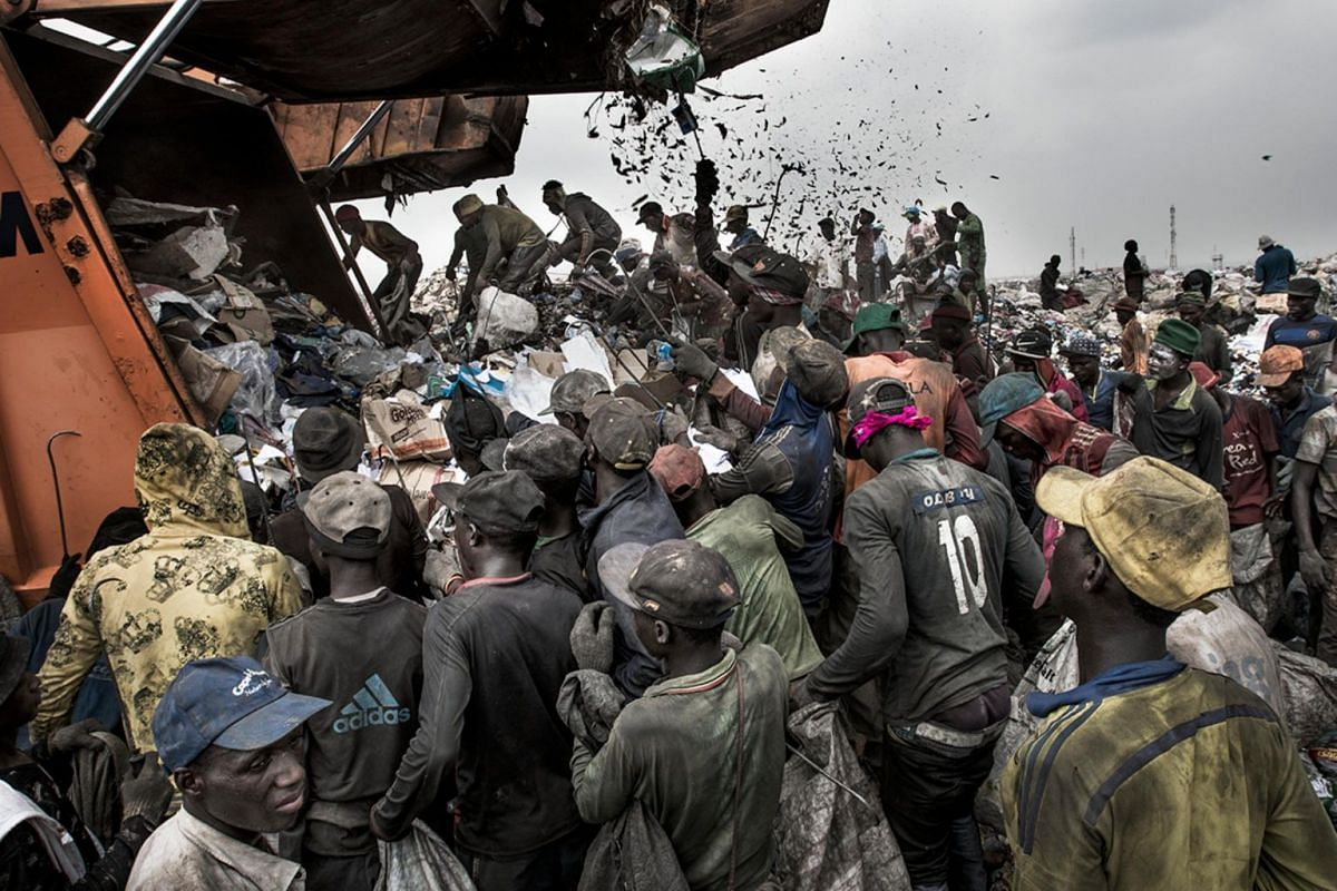 People wait to sort through waste for recyclable and saleable material, as a garbage truck arrives at the Olusosun landfill in Lagos, Nigeria, on Jan 21, 2017.