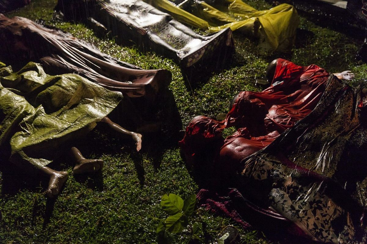 The bodies of Rohingya refugees are laid out after the boat in which they were attempting to flee Myanmar capsized about eight kilometres off Inani Beach, near Cox's Bazar, Bangladesh, on Sept 28, 2017. Around 100 people were on the boat before it ca