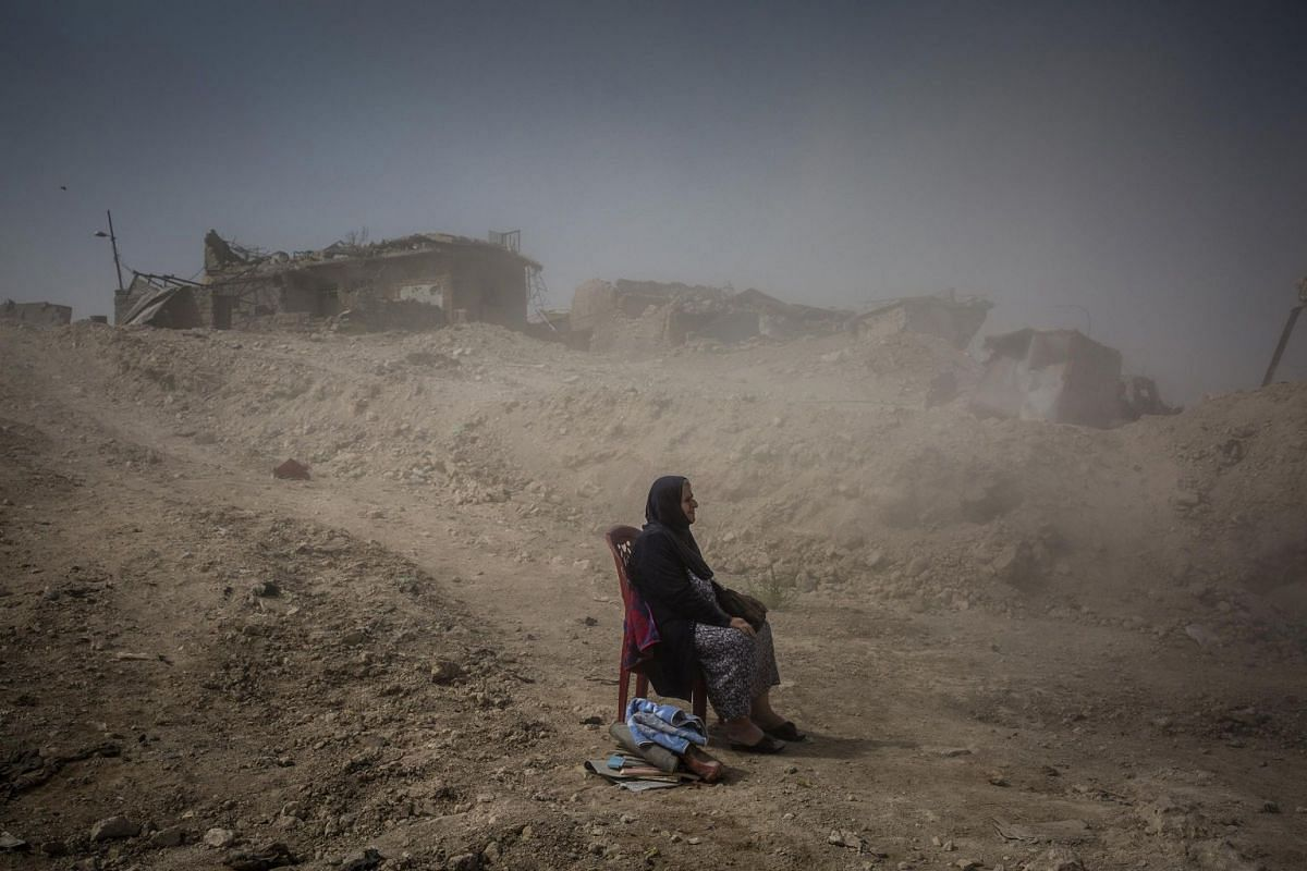 Nadhira Aziz looks on after west Mosul had been retaken, on Sept 16, 2017, as Iraqi Civil Defense workers excavate the remains of her sister and niece from her house in the Old City, where they were killed by an airstrike in June. She sat in her chai