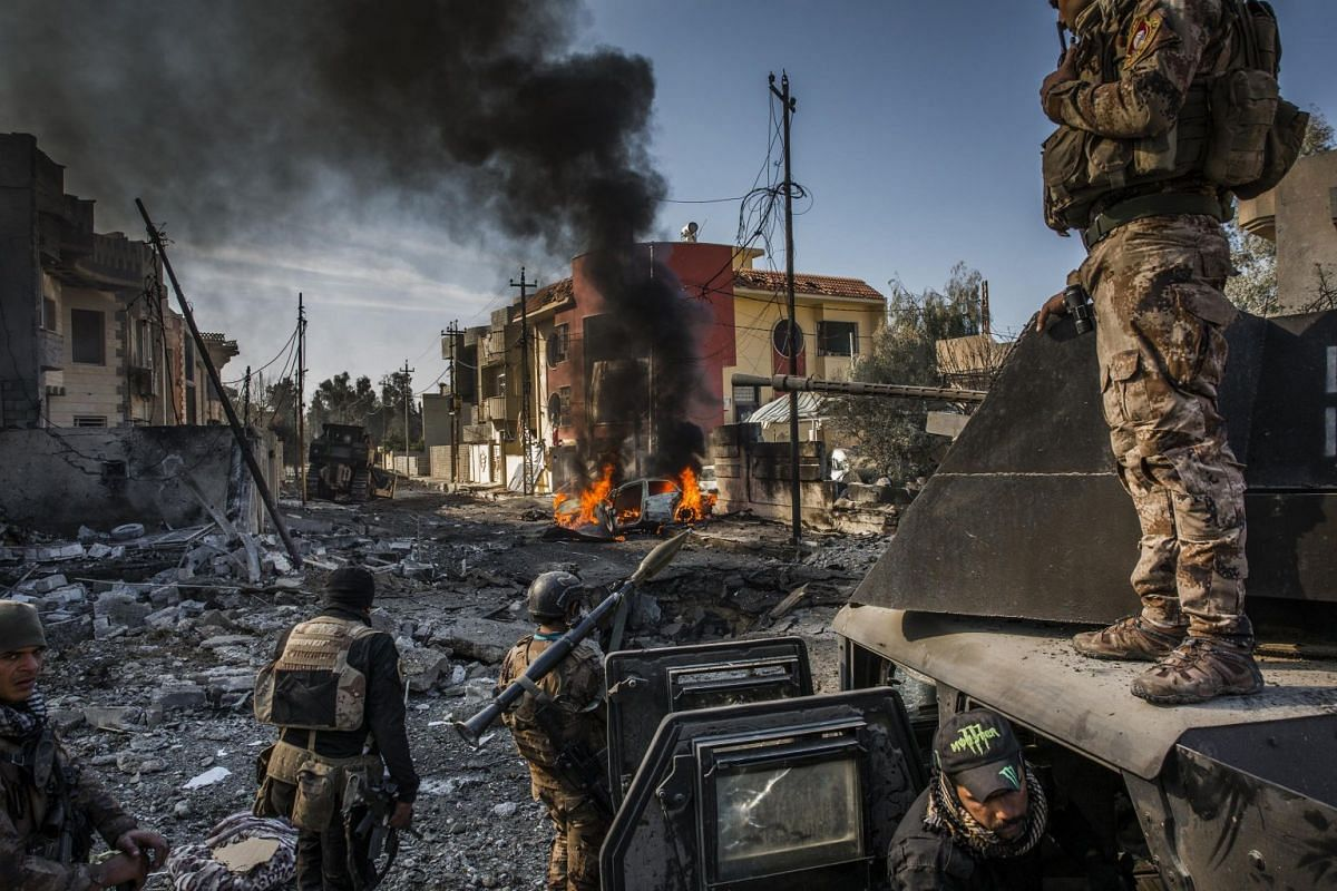 Iraqi Special Forces soldiers survey the aftermath of an attack by an ISIS suicide car bomber, who managed to reach their lines in the Andalus neighborhood, one of the last areas to be liberated in eastern Mosul, on Jan 16, 2017.