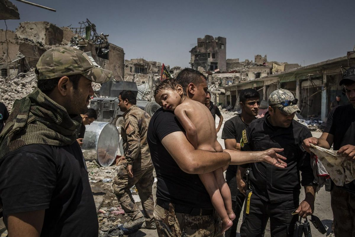An unidentified young boy, who was carried out of the last ISIS-controlled area of the Old City by a man suspected of being a militant, is washed and cared for by Iraqi Special Forces soldiers, on July 12, 2017. The soldiers suspected that the man ha