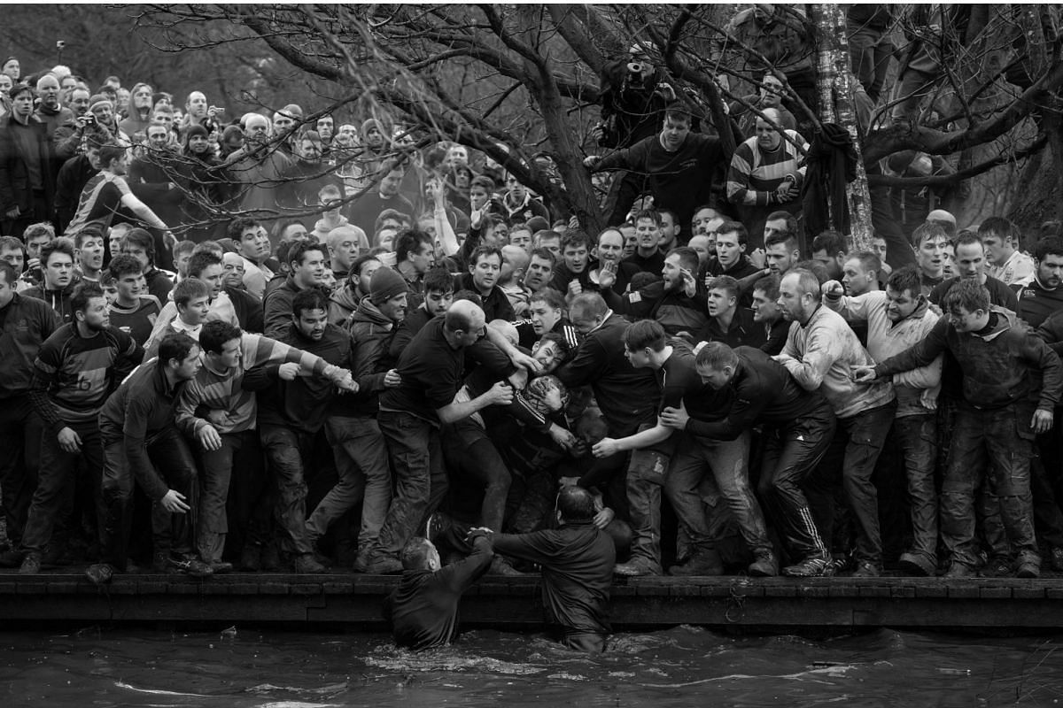 Members of opposing teams, the Up'ards and Down'ards, grapple for the ball during the historic, annual Royal Shrovetide Football Match in Ashbourne, Derbyshire, UK, on Feb 28, 2017. The game is played between hundreds of participants in two eight