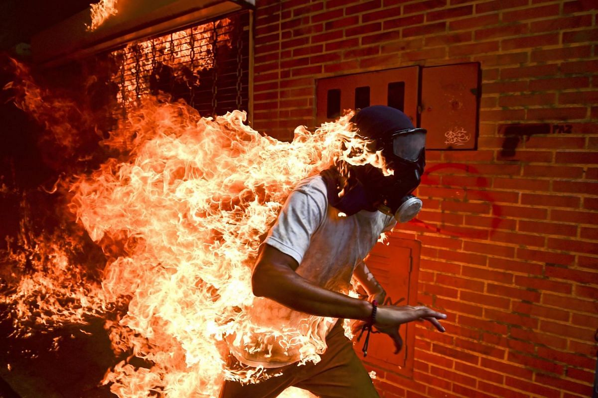 José Víctor Salazar Balza, 28, catches fire amid violent clashes with riot police during a protest against President Nicolás Maduro, in Caracas, Venezuela, on May 3, 2017. President Maduro had announced plans to revise Venezuela's democratic sys