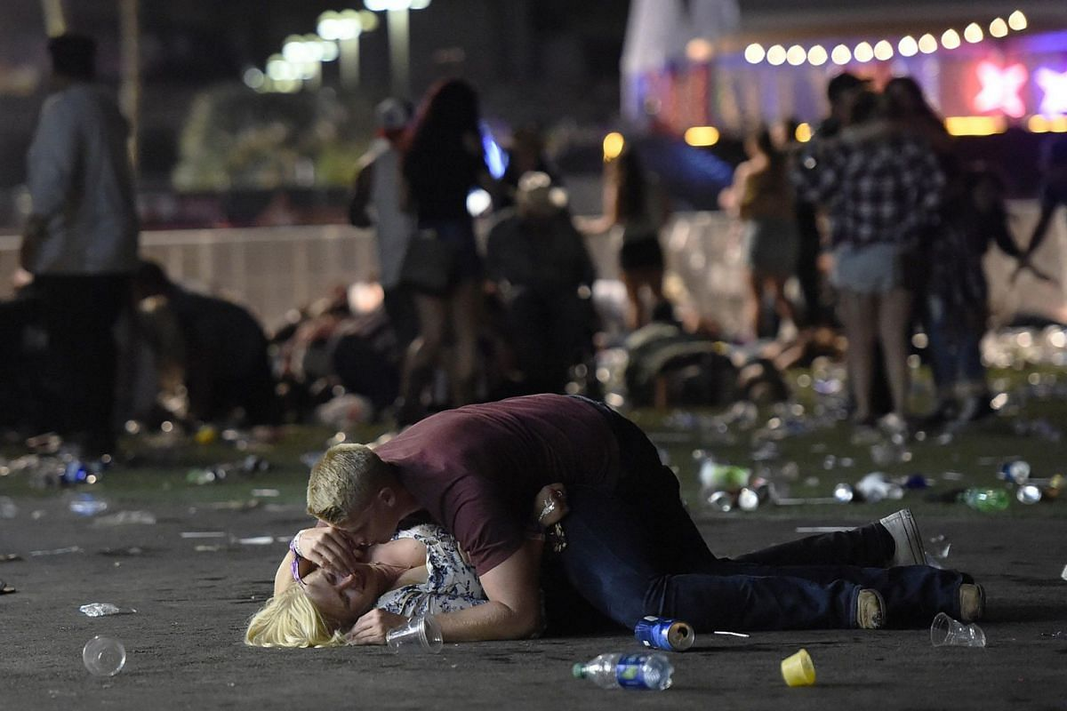 A man lies protectively on top of a woman, as others flee the shooting, after a gunman opens fire on concertgoers at the Route 91 country music festival in Las Vegas, USA, on Oct 1, 2017.