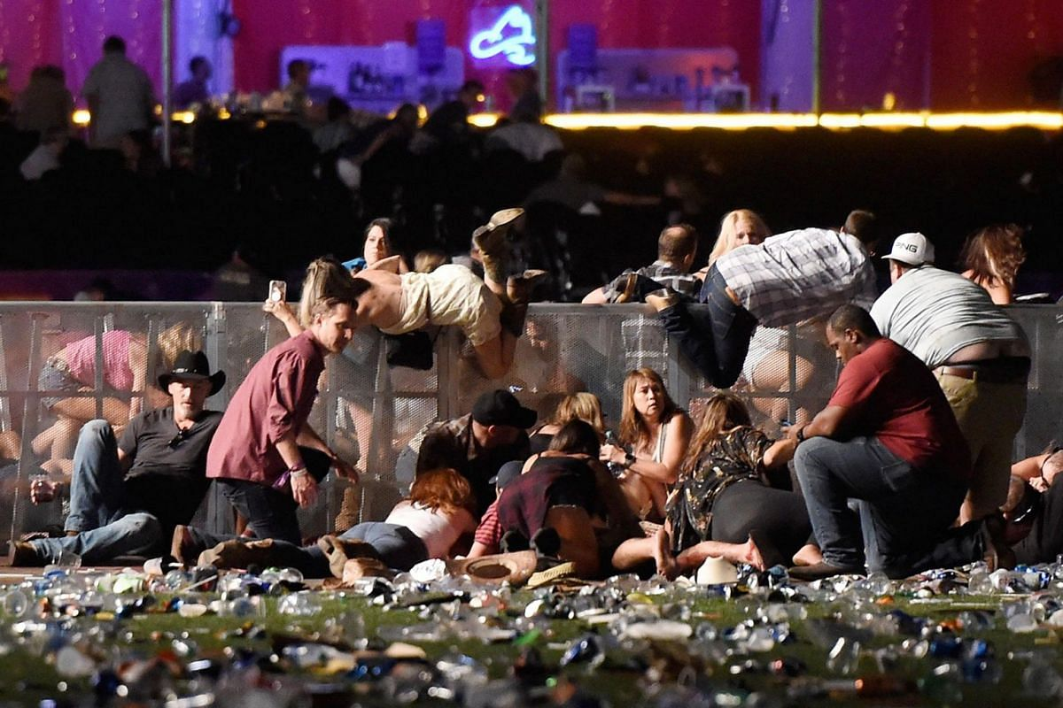 People scramble for shelter after gunshots ring out at the Route 91 country music festival in Las Vegas, USA, on Oct 1, 2017.