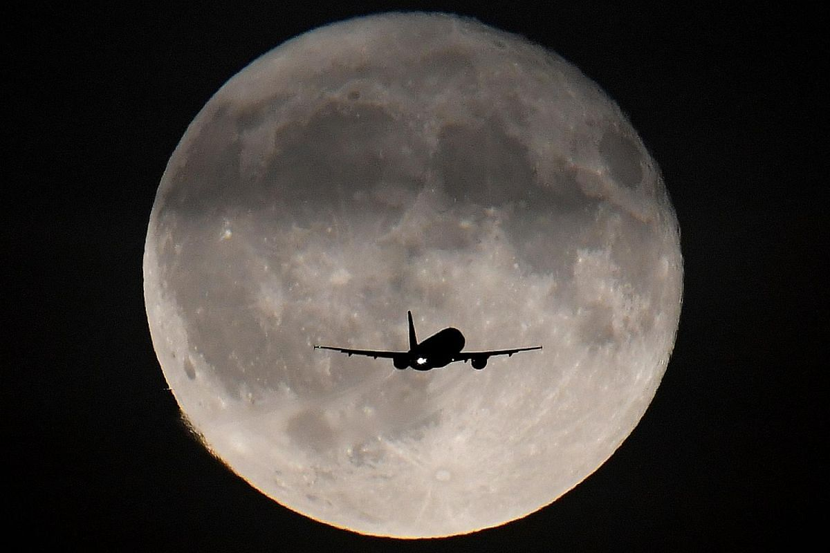 A passenger plane is seen with the moon behind it as it begins its final landing approach to Heathrow Airport in London, Britain, on Sept 25, 2018.