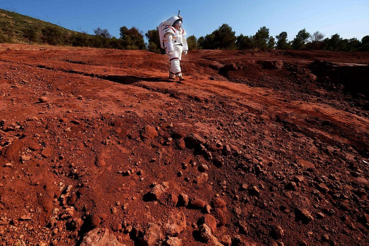 French M6 TV channel presenter Eglantine Emeye, wearing a Gandolfi 2 space suit, from Comex space division, walks for a TV programme on Sept 25, 2018 in Vitrolles, near Marseille, southern France.