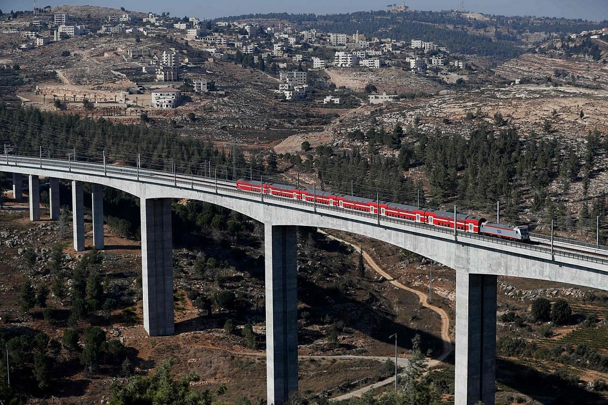 This picture taken on Sept 25, 2018, on the outskirts of Jerusalem, shows a new high speed train travelling between Jerusalem and Israel's Ben Gurion International Airport with the Palestinian village of Beit Iksa in the background.