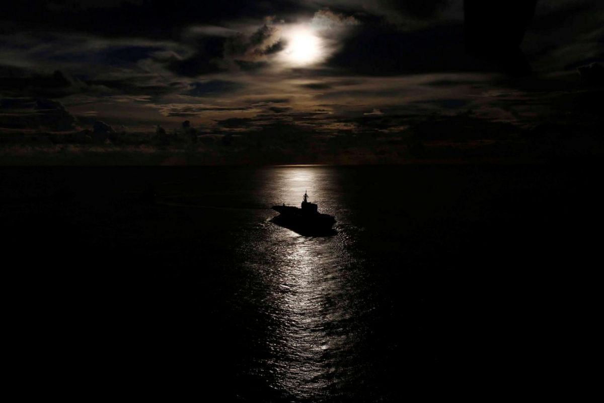Japanese helicopter carrier Kaga is silhouetted against the reflection of the sun on the ocean during a joint naval drill with British frigate HMS Argyle and Japanese destroyer Inazuma in the Indian Ocean, on Sept 26, 2018.
