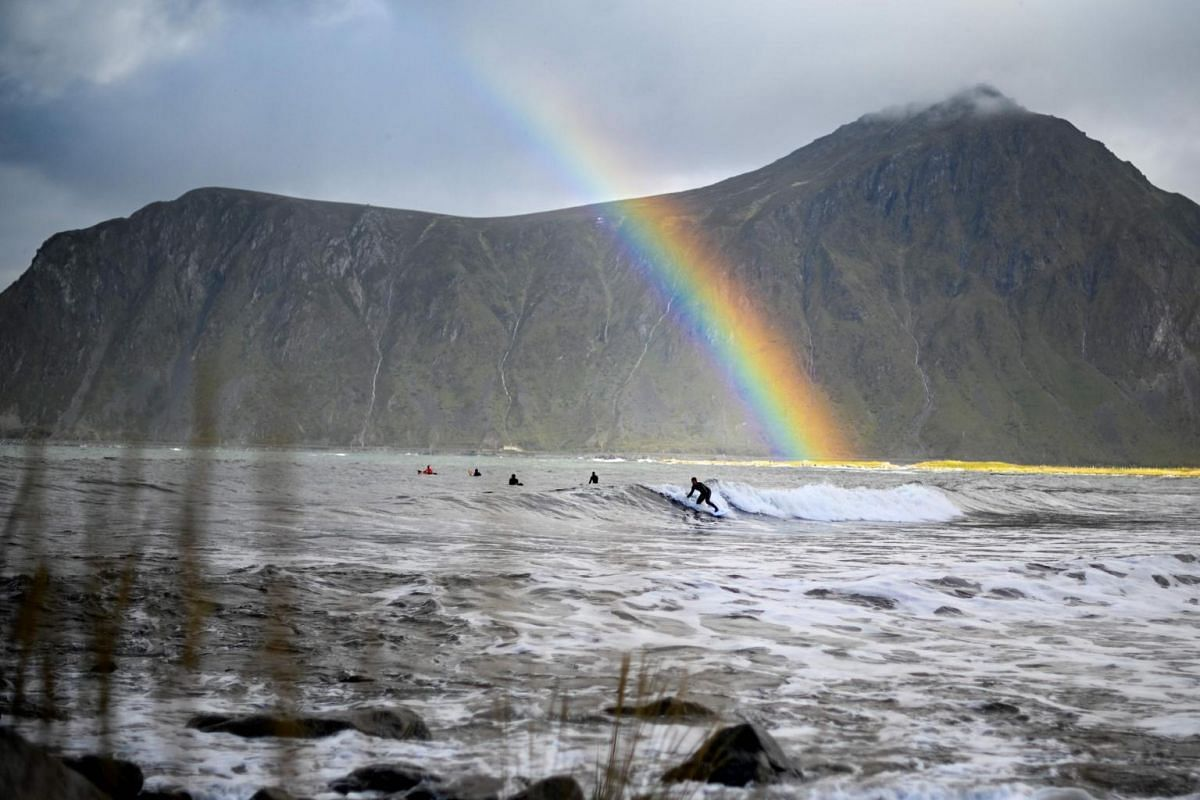 Surfer Anker Olsen Frantzen, 17, of Norway, riding a wave under a rainbow during a free surf session on Sept 26, 2018, in Flakstad, northern Norway, at the eve of the Lofoten Masters 2018.
