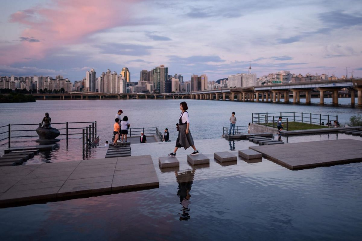 A woman walks over stepping stones before the Han river and Seoul's skyline at Yeouido park, on Sept 26, 2018.