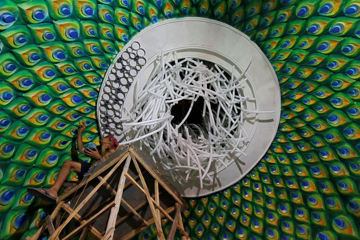A man applies finishing touches to a decorative ceiling of a pandal, a temporary platform, for the upcoming Hindu festival of Durga Puja in Kolkata, India, September 27, 2018. PHOTO: REUTERS