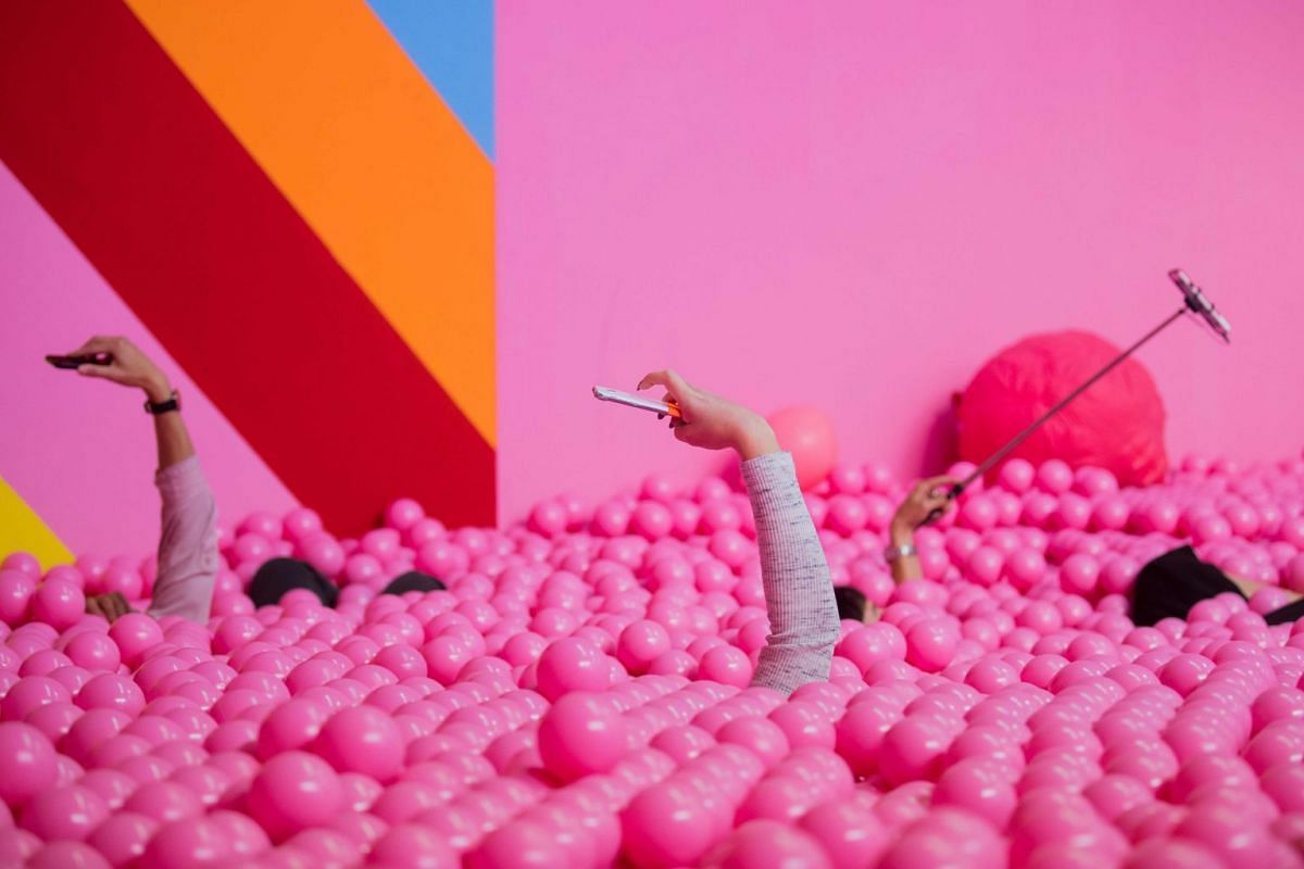 Visitors use their mobile devices to take pictures of themselves posing in a pink ball bath at the Supercandy Pop-Up Museum in Cologne, western Germany, on September 27, 2018. - Until December 30, 2018, the museum offers 20 interactive installations