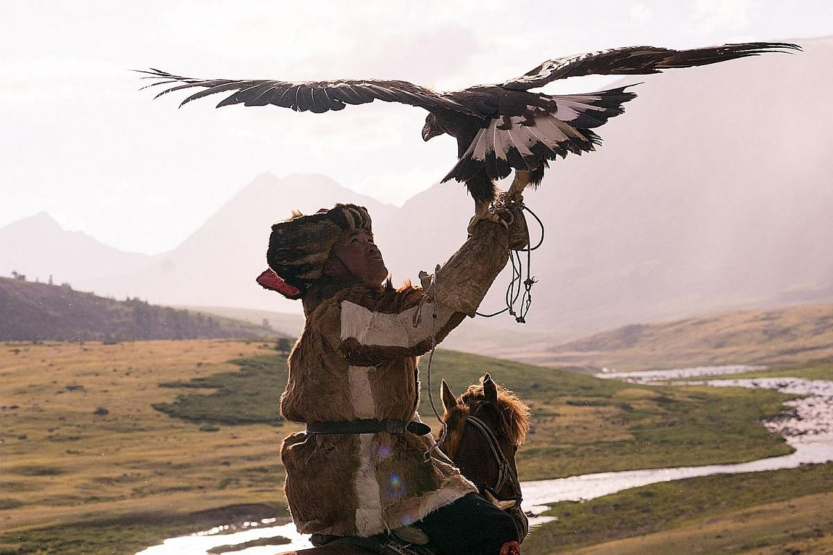 An eagle hunter in the Altai Mountains (above) and a little boy on his horse at the Khuitas valley camp (below). From top: A series of gers; a frozen lake on the way to the Khuitas valley; and a Kazakh woman milking sheep. Right: Setting off in a veh