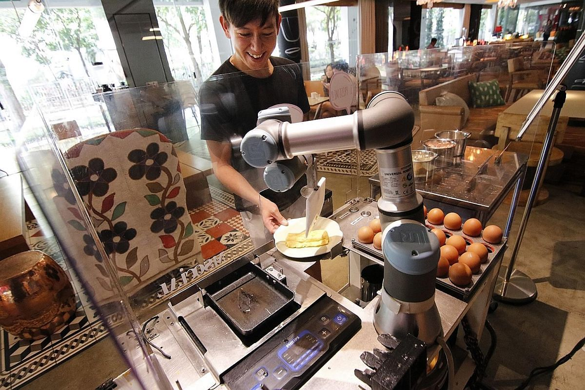 M Social Singapore hotel guest Eugene Pang getting an omelette cooked by AUSCA, a robotic egg chef at the breakfast buffet. Robot butlers Sophie (left) and Xavier (right) deliver items such as towels, toiletries and bottled water to the 223 guest roo